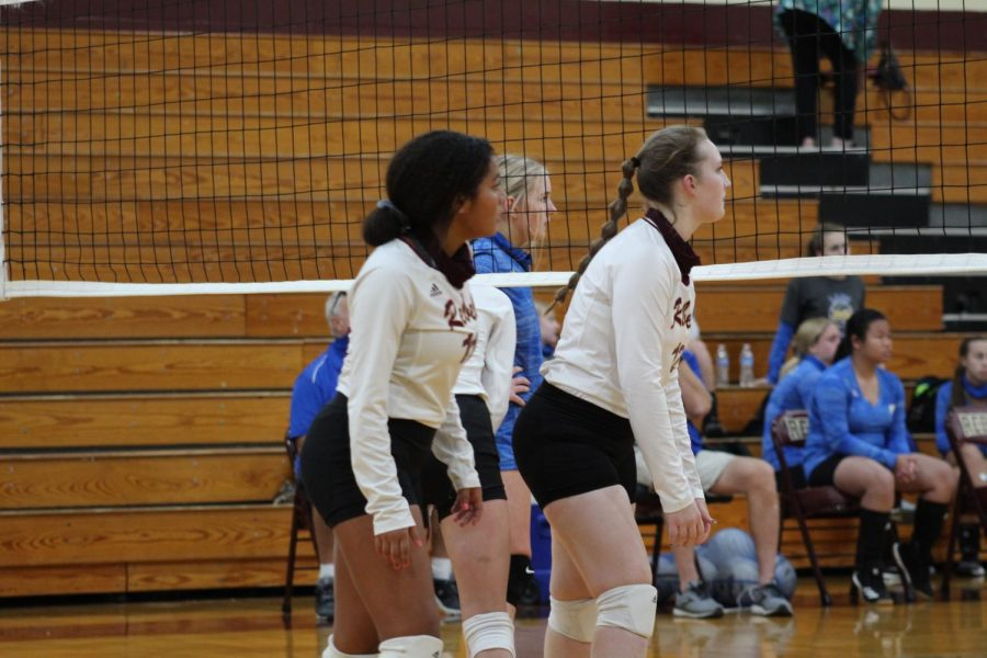 Volleyball players prepare to defend their court.