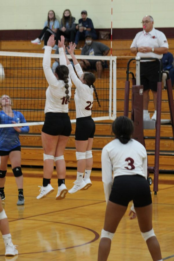 Lady Rebels Volleyball blocks ball from going over the net.