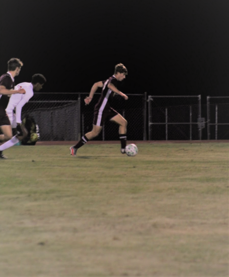 Soccer player takes the ball on a run down the field.