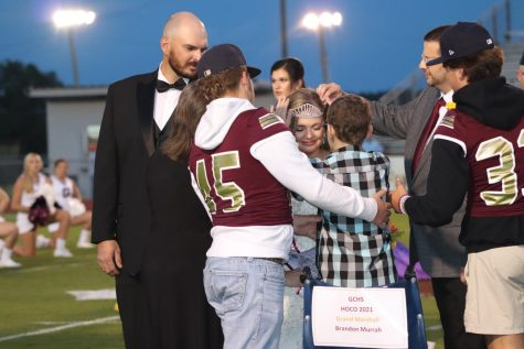 Grand Marshall Brandon Murrah crowns 2021 homecoming queen Carlie Herrington.